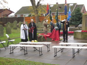 Clergy and others gathering for a Remembrance Day service at a cemetery